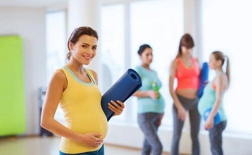 Signora con pancione sorride prima di un allenamento di pilates in gravidanza