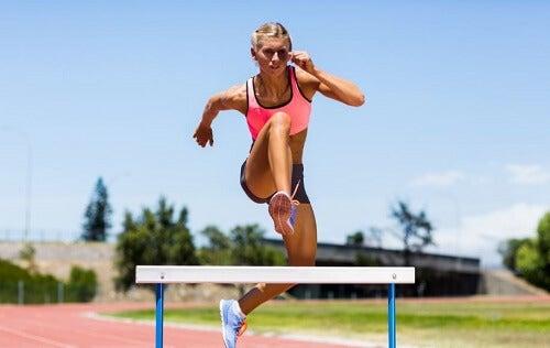 Una ragazza salta un ostacolo in corsa