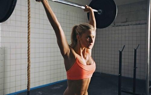 Ragazza bionda alza bilanciere in allenamento