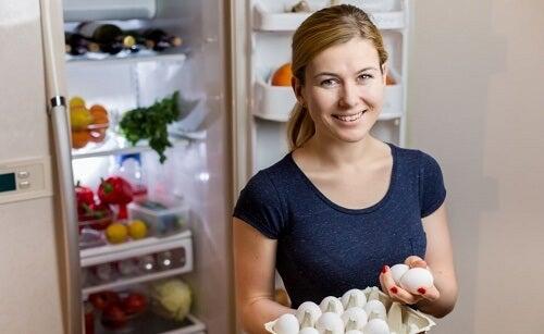 Ragazza sorride davanti al frigo tenendo delle uova