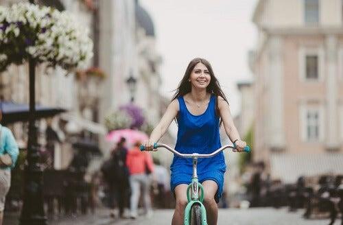 Ragazza con abito blu pedala in bici