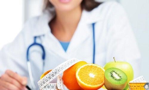 dottoressa con davanti agrumi e metro peso