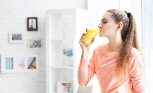ragazza beve un succo di arancia