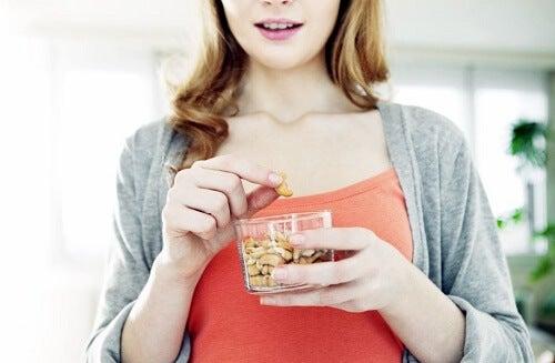 una ragazza intenta a mangiare della frutta secca