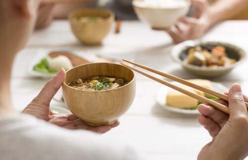 Ragazza mangia in modo orientale