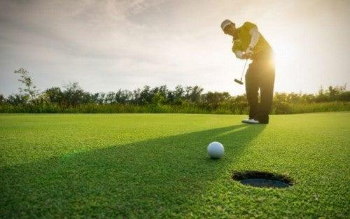Uomo gioca a golf al tramonto