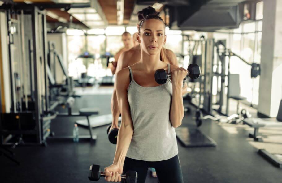 ragazza cerca di ottenere buoni risultati con i pesi