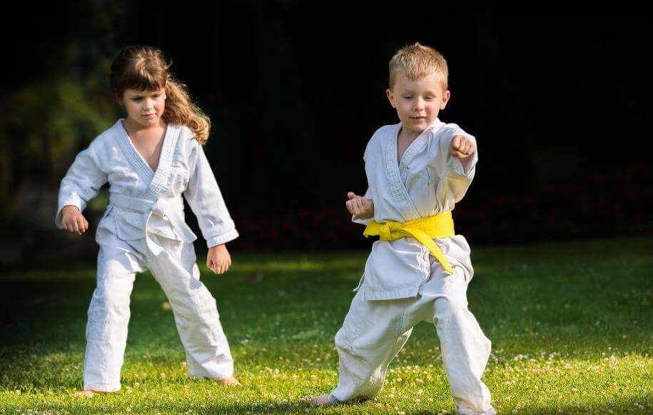 bambino e bambina praticano arti marziali sul prato