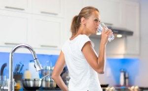 donna che beve acqua in cucina