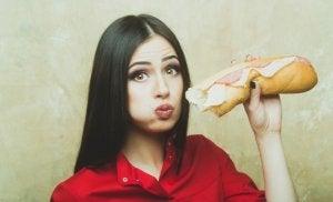 miti sulla dieta: donna che mangia panino con il prosciutto