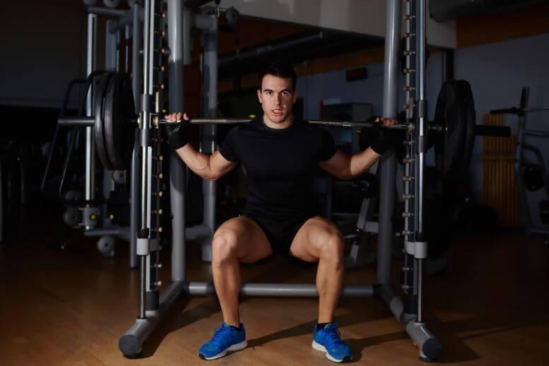 un ragazzo fa squat con la barra nella routine busto-gambe