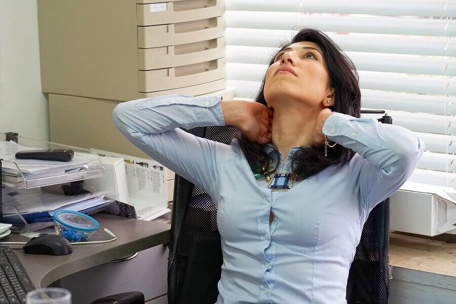 donna fa stretching del collo in ufficio