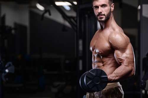 Uomo allena braccia in palestra