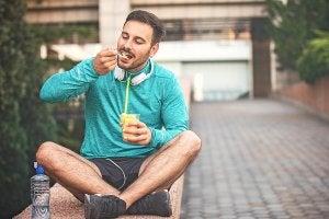 sportivo che mangia frutta seduto sul muretto