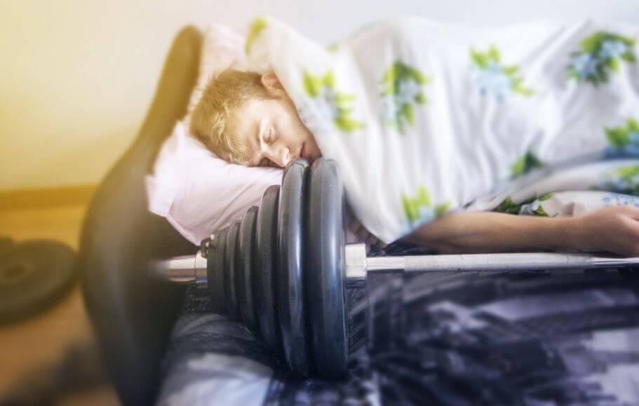 Atleta che dorme accanto a un bilanciere