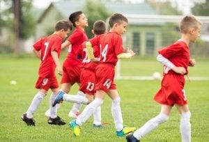 Bambini che fanno un allenamento di calcio. Benefici degli sport di squadra.