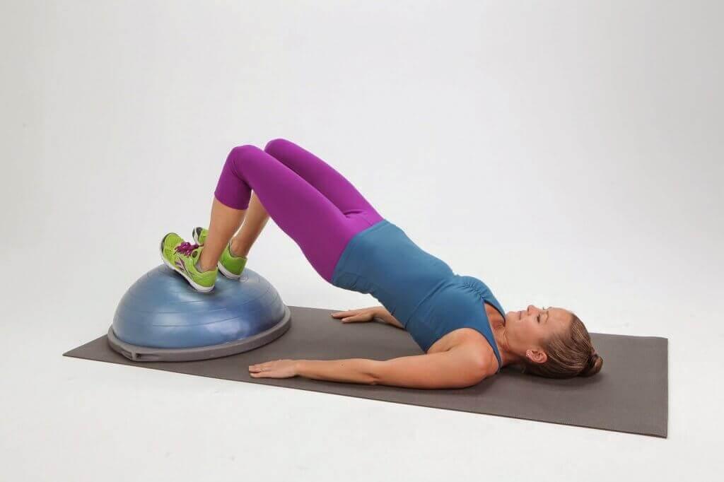 Ragazza che esegue il ponte rialzato tra gli esercizi per i muscoli ischiocruriali