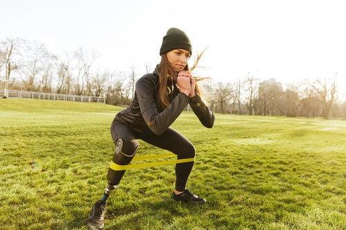 Ragazza che fa squat con una protesi