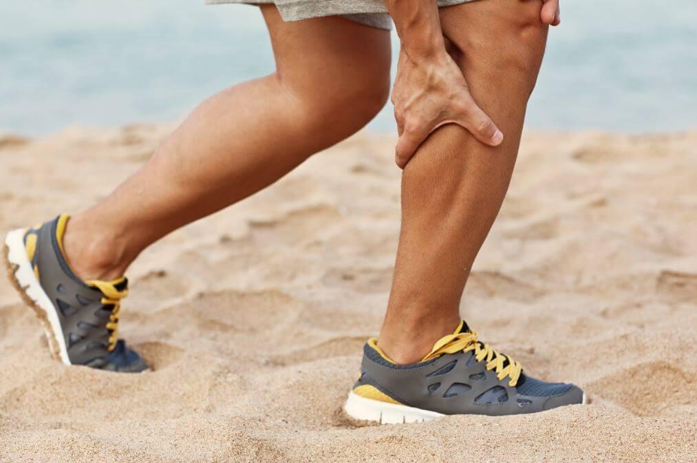 Persona con strappo muscolare mentre cammina sulla sabbia