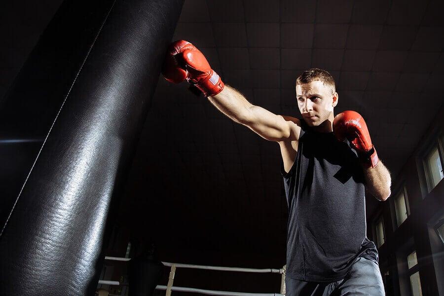 Uomo con sacco perché il pugilato è tra gli sport per combattere lo stress