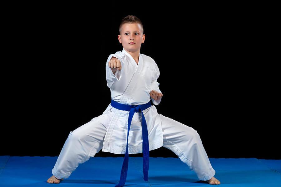 Bambino che fa karate. Sport olimpici requisiti.