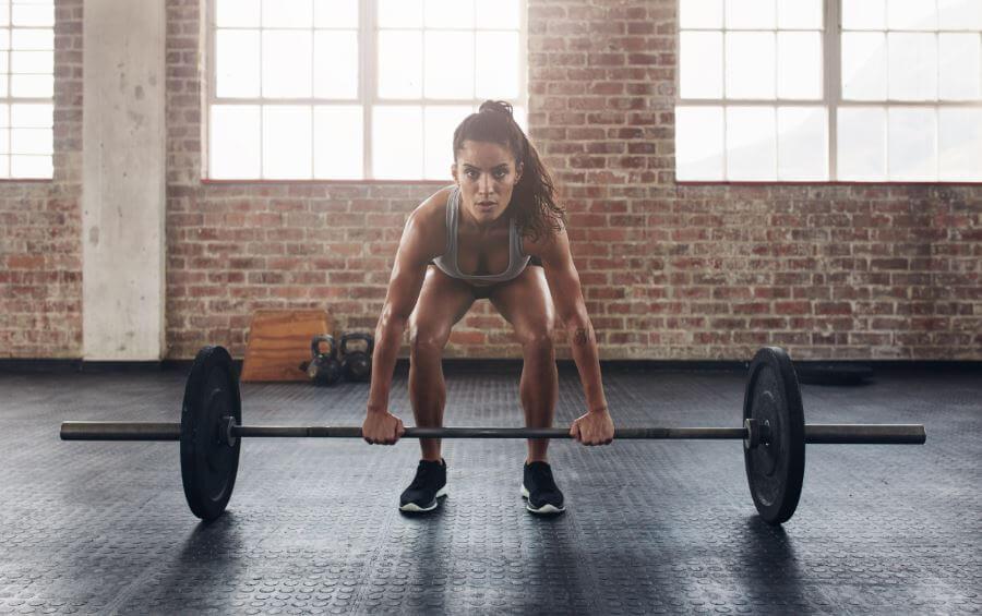 Ragazza che esegue il deadlift tra gli esercizi base del crossfit