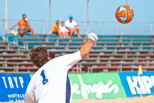 Portiere di calcio durante una partita sulla sabbia