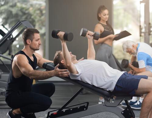 Allenamento metabolico: uomo fa pesi in palestra.
