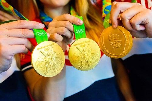 Atlete mostrano le medaglie. Carta olimpica.