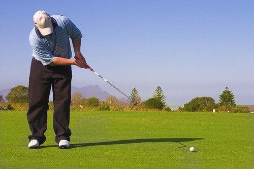 Uomo intento a giocare a golf