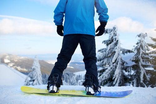 Uomo fa snowboard