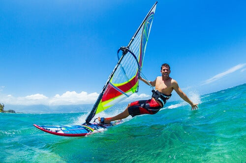 Windsurf: uomo fa windsurf su un'onda