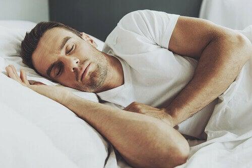 Sonno brucia grassi: uomo dorme su lenzuola bianche
