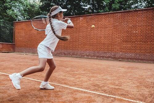Tennista junior che gioca contro un muro