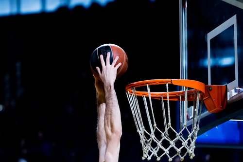 Giocatore porta la palla a canestro.