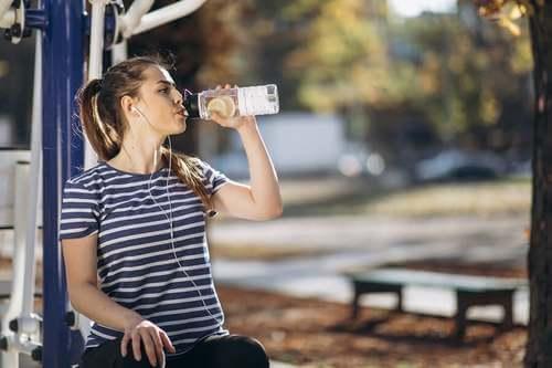 Idratazione durante lo sport: ragazza con maglietta a righe beve