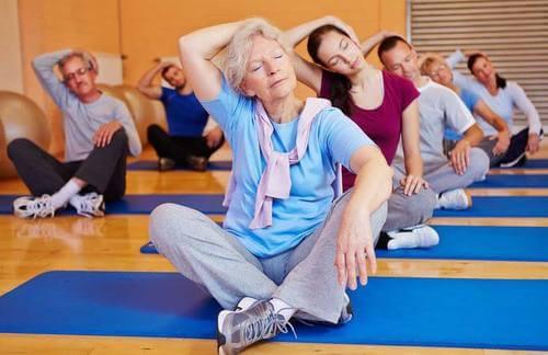 Gruppo di anziani fanno yoga.