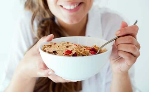 Ragazza mangia cereali a colazione.