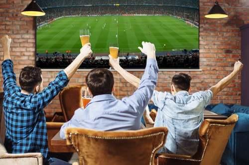 Tre uomini che guardano una partita di calcio.