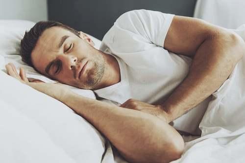 Uomo che riposa a letto.