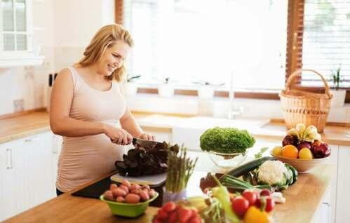 Donna che taglia delle verdure in cucina.