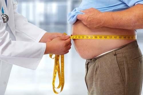 Un medico misura la pancia di un paziente.