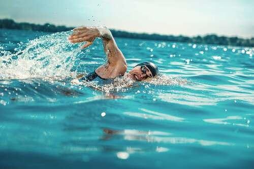 Atleta che nuota in acque libere.