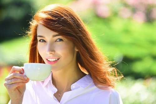Donna che beve una tazza di caffè.