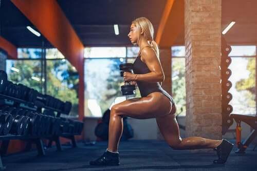 Donna sudata che fa pesi in palestra.