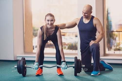 Ragazza che si allena con il personal trainer.