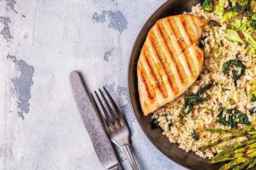 Pollo alla griglia con riso integrale e asparagi.