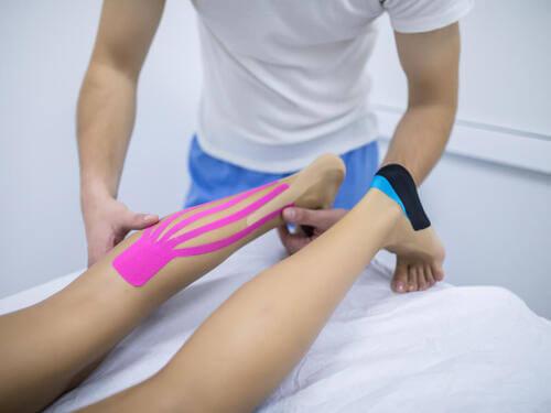 Il fisioterapista applica il bendaggio delle gambe al paziente.