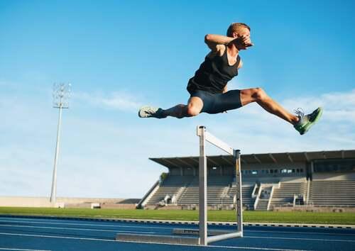 Atleta che salta un ostacolo.