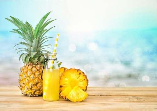 Ananas e succo giallo su una spiaggia.